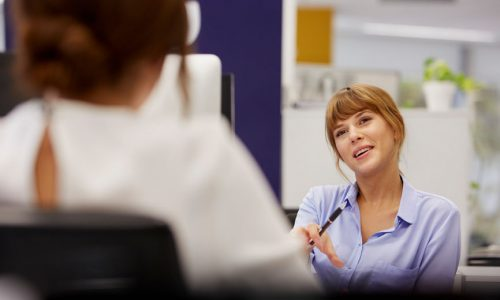 Smiling businesswoman talking to female colleague in office