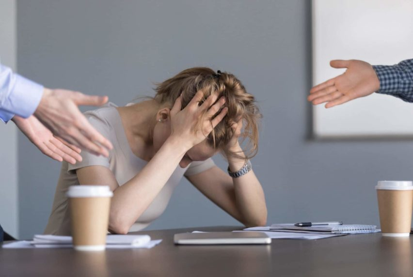 Stressed young businesswoman holding head in hands suffering from unfair gender discrimination at work concept, female employee frustrated by male colleagues bullying humiliating woman at workplace