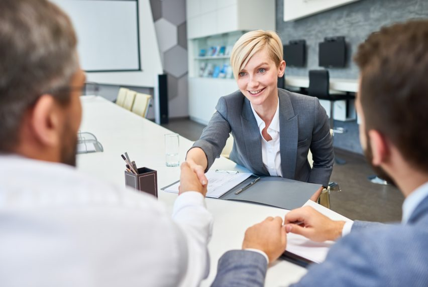 Portrait of young successful businesswoman shaking hands with partners at meeting table in board room after successful deal