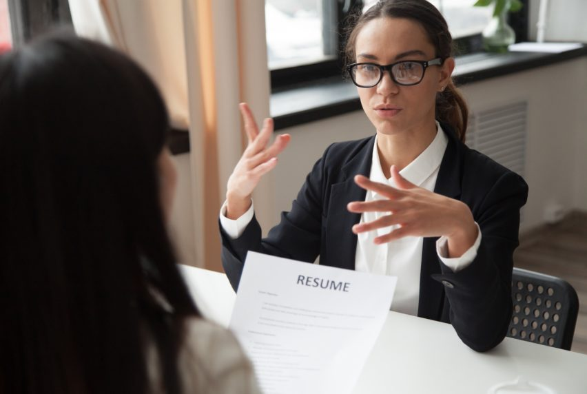 Confident millennial female applicant in glasses talking at job interview answering questions, vacancy candidate making first impression concept and introducing herself speaking to hr holding resume